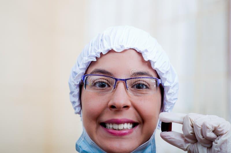 戴鼓胀盖帽和眼镜的特写镜头特写女性护士阻止照相机微笑的两个药片胶囊 免版税库存图片
