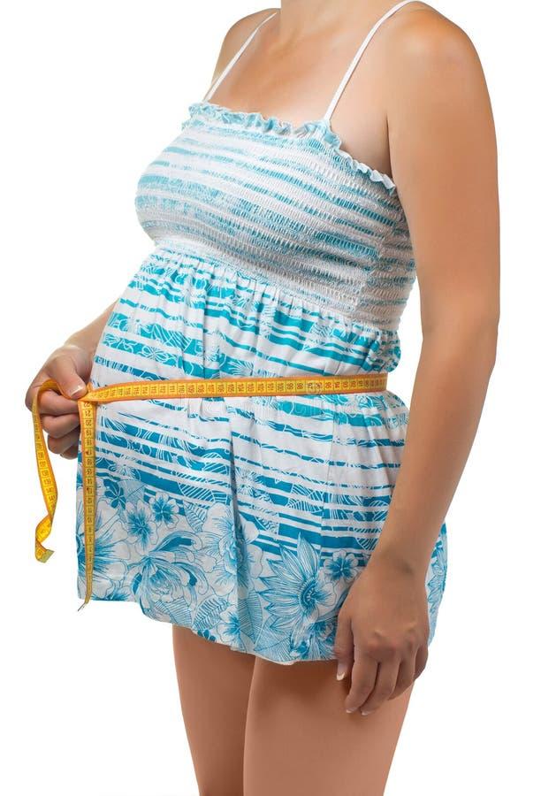 鼓起她的评定孕妇 免版税库存图片