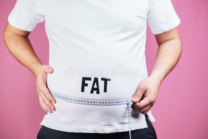 鼓起油脂,暴食者 有措施磁带的肥胖人 库存照片