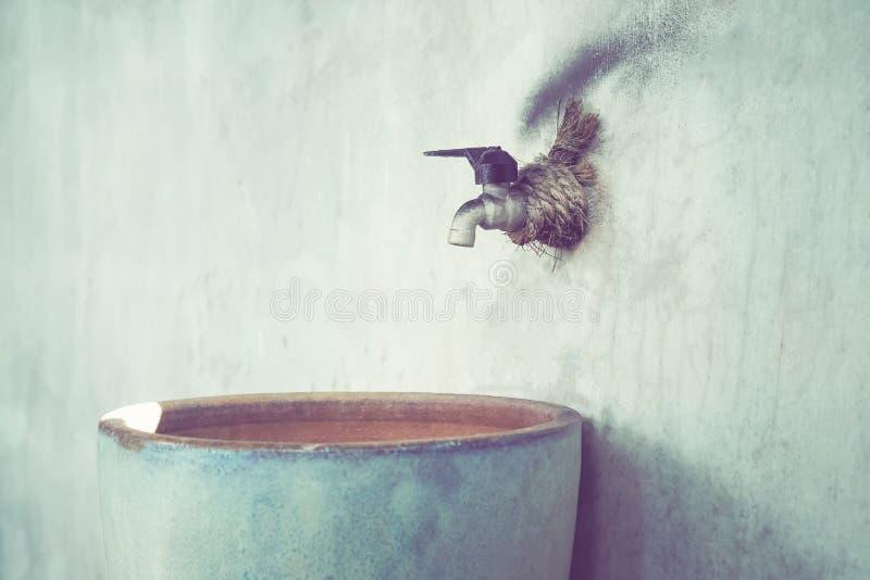 龙头连接墙壁并且有人的水库能使用 葡萄酒口气 免版税图库摄影