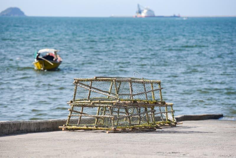 龙虾和捕蟹篓堆积了在海湾海洋背景的鱼网捉住的渔船 免版税图库摄影