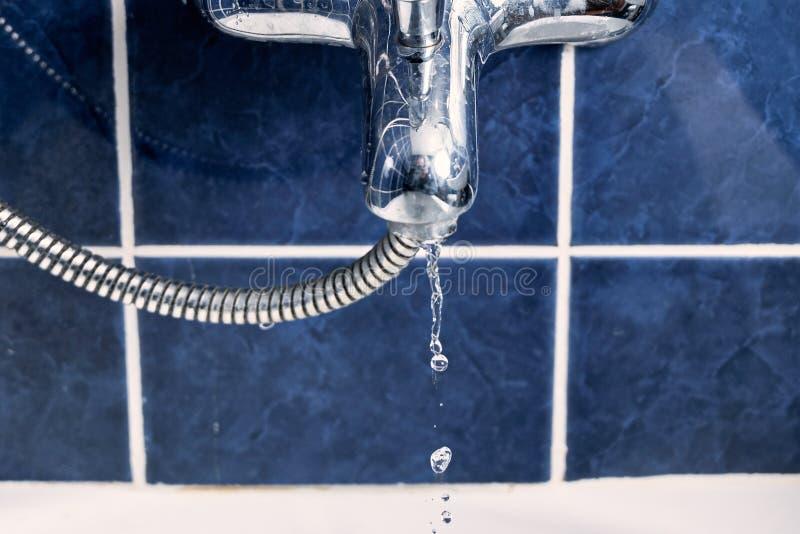 水龙头正面图在有在空气结冰的水流程的浴屋子里 免版税库存图片