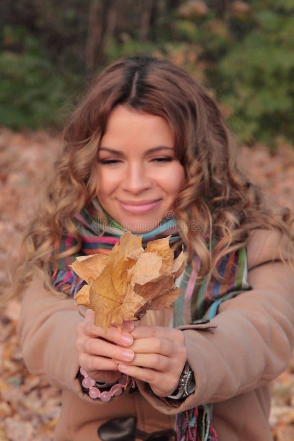 年轻,微笑和俏丽的妇女在秋天公园 免版税库存图片