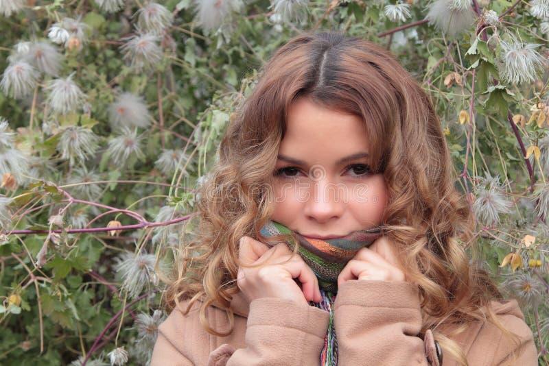 年轻,微笑和俏丽的妇女在秋天公园 免版税图库摄影