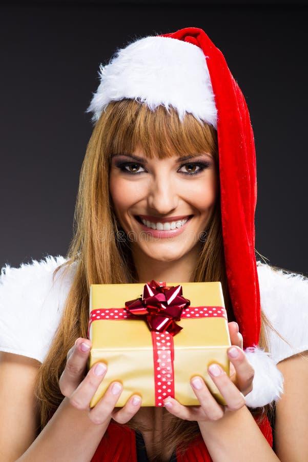 年轻,性感的妇女圣诞老人画象有礼物盒的 免版税库存照片