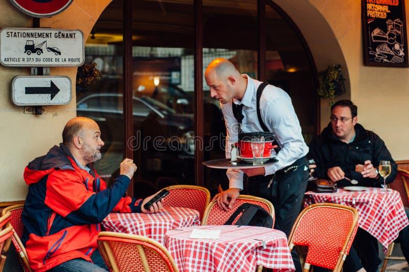 巴黎,法国- 2015年11月4日:人与侍者谈话在stree 免版税库存照片