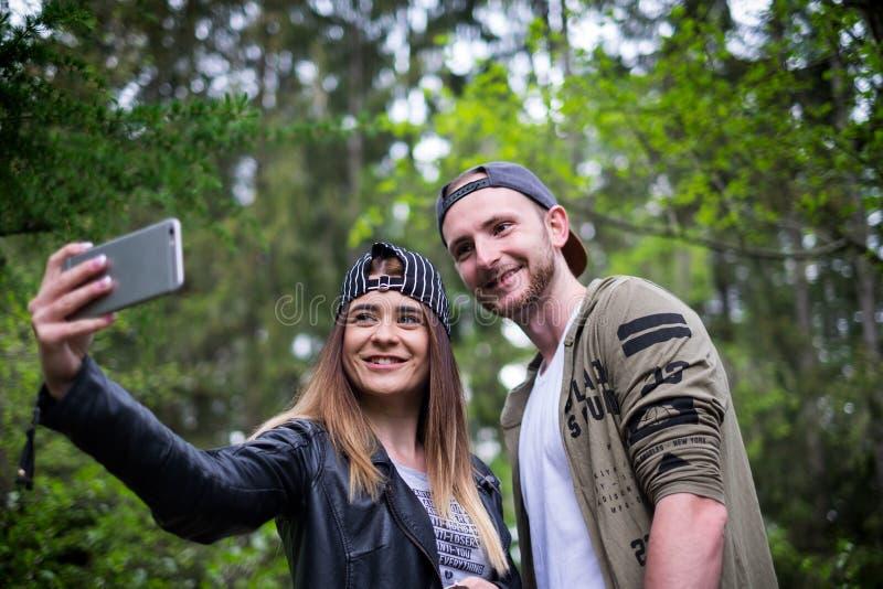 年轻,现代的夫妇举行手机和笑 现代关系的概念 关闭坐行家的人  库存图片