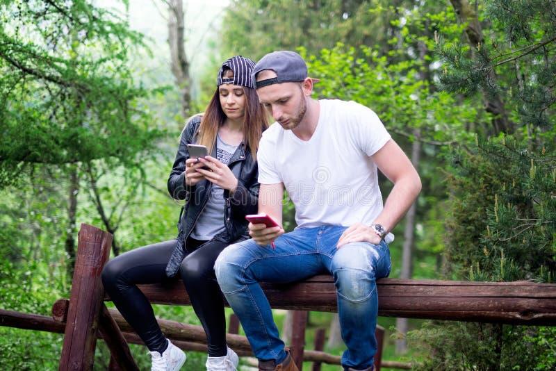 年轻,现代的夫妇举行手机和笑 现代关系的概念 关闭坐行家的人  免版税库存图片
