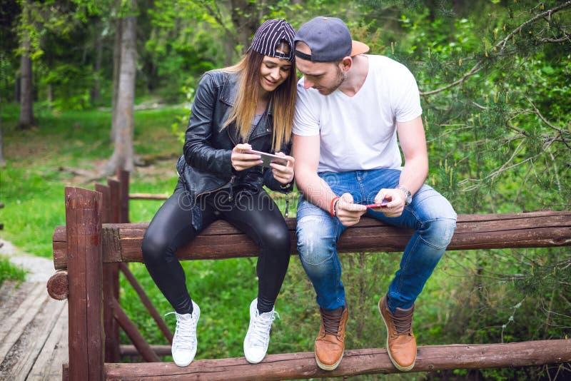 年轻,现代的夫妇举行手机和笑 现代关系的概念 关闭坐行家的人  免版税库存照片