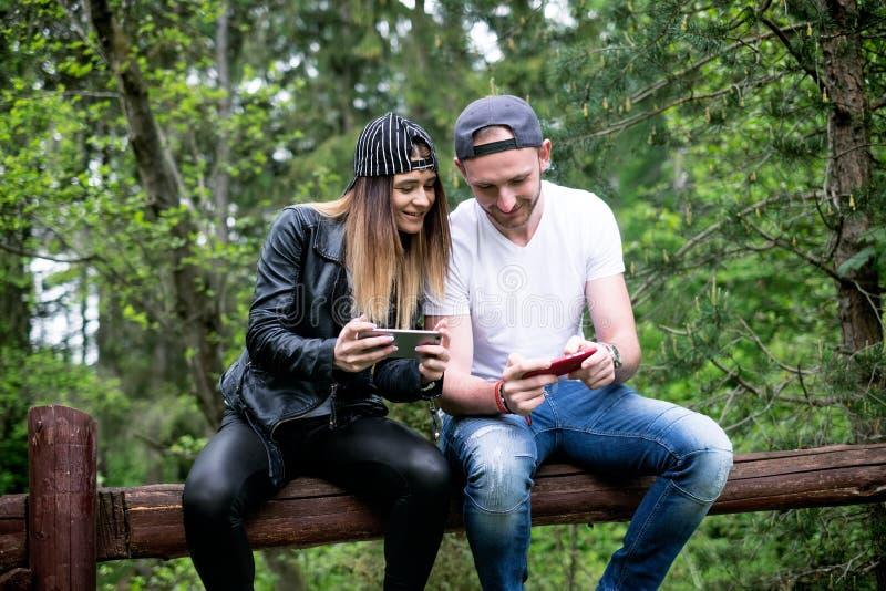 年轻,现代的夫妇举行手机和笑 现代关系的概念 关闭坐行家的人  库存照片