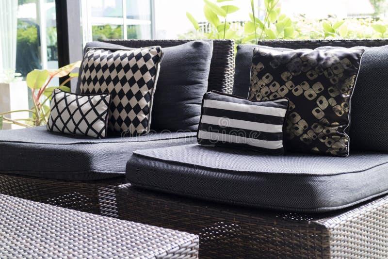 黑,白色坐垫和枕头在藤椅 免版税库存图片