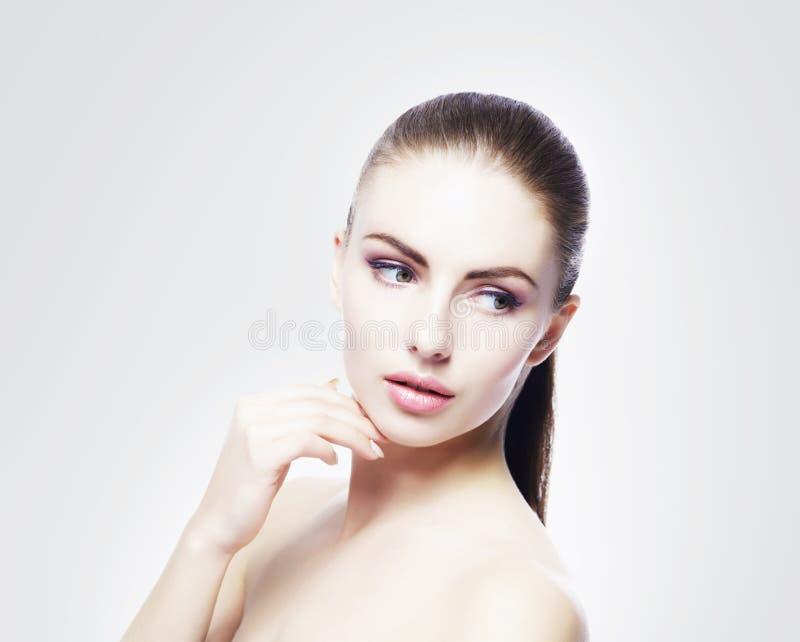 年轻,美丽和健康妇女画象:在冷的灰色背景 免版税库存照片