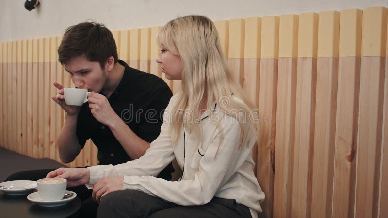 年轻,美好的夫妇有日期在咖啡馆,谈的和饮用的咖啡 图库摄影