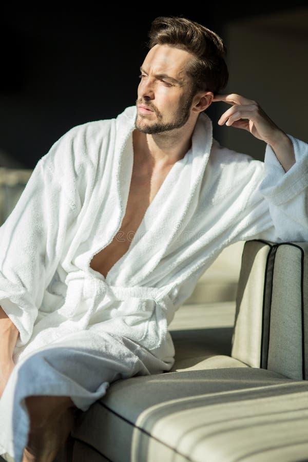 年轻,肌肉,英俊,健康男性放松在a的一个长沙发 免版税库存照片