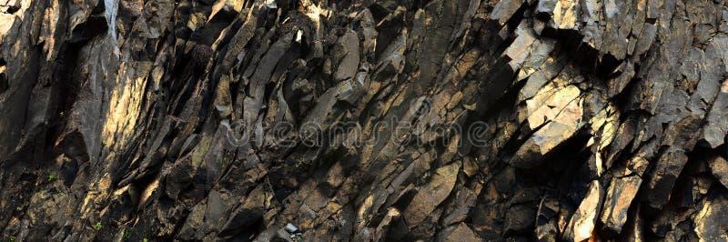 黑,金黄岩石-抽象火山的石背景 库存照片