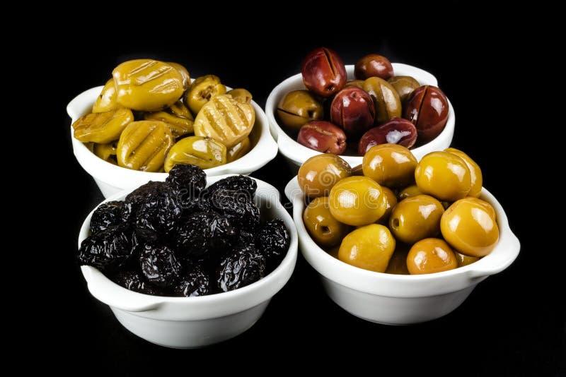 黑,绿色,烤和桃红色橄榄在碗 免版税库存图片