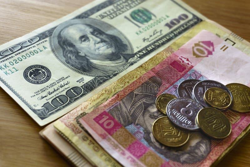 1,2 hryvnias被堆积对100美国美元,减少hryvnias和美元乌克兰金属硬币  库存图片