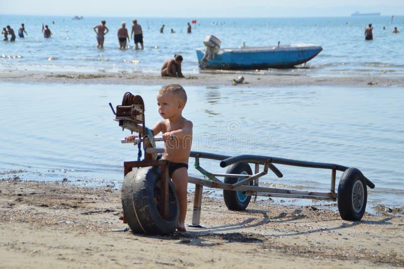 :地方男孩使用与在海滩的一辆老海喷气机拖车都拉斯 免版税库存照片