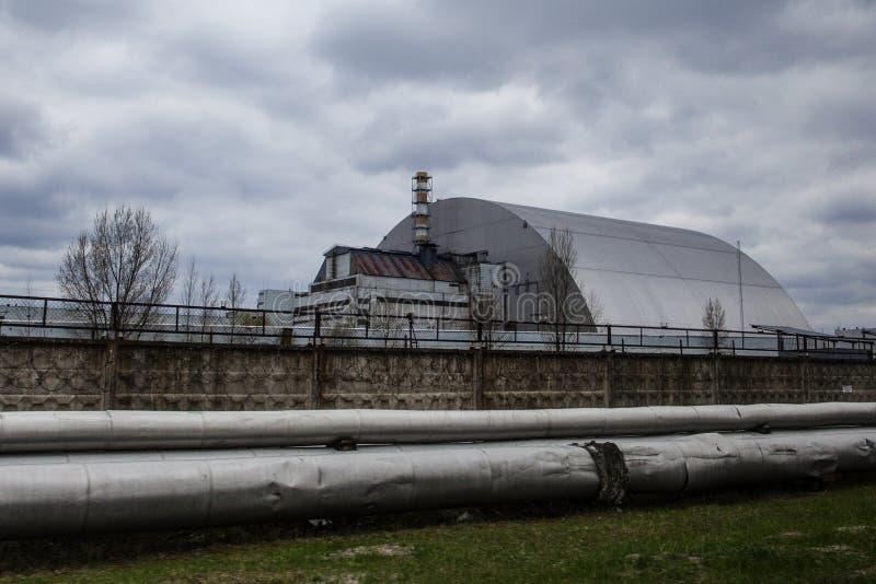 :被毁坏的反应器4和切尔诺贝利清算人的纪念品的看法 免版税库存图片