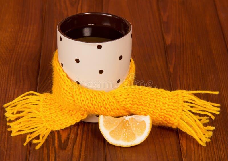 �up av varmt te med citronen som slås in i gul halsduk royaltyfri bild
