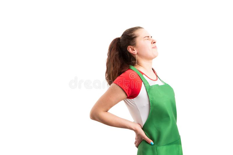Female supermarket or hypermarket worker suffering back pain royalty free stock photo