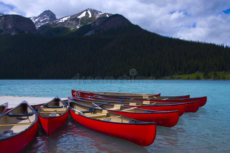 0range canoes at lake louise. Canoes in lake louise - banff national park, canada royalty free stock photo