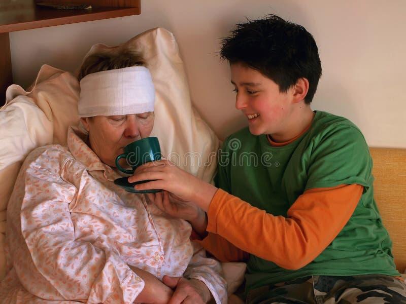 1个男孩喂养病的妇女 免版税库存图片