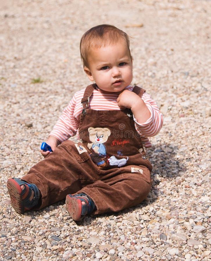 1婴孩老小卵石坐的年 库存照片