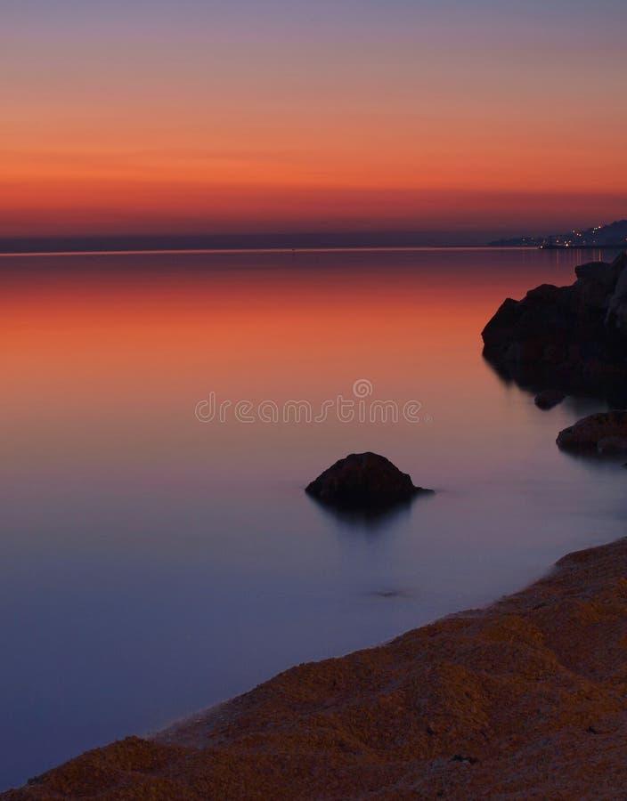 1 hav stenar solnedgång arkivbild