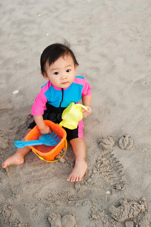 1 year old Asian Chinese toddler. Making sand castles on the beach royalty free stock photo