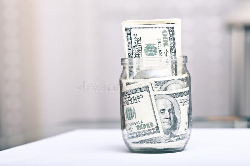 100 banconote dei dollari US In un vaso di vetro immagini stock