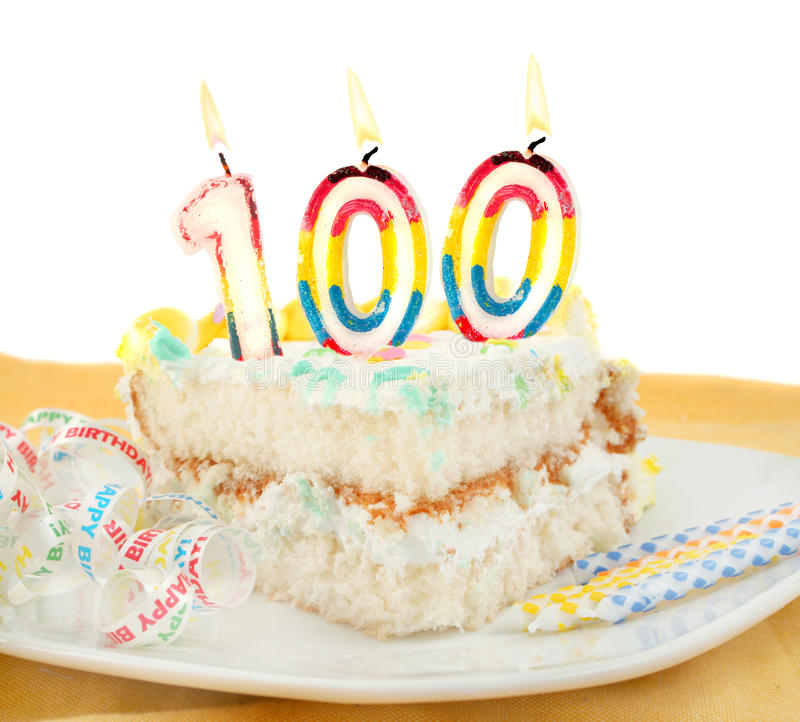 100 year birthday or anniversary cake. Slice of frosted festive birthday cake with candles and ribbon celebrating 100 year old birthday or anniversary stock images
