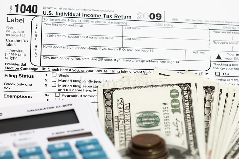 1040 tax form. With calculator and dollars stock photography