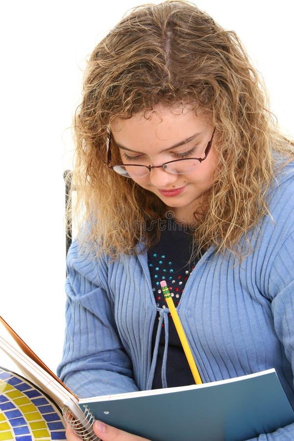 12 años hermosos de la escritura de la muchacha en cuaderno fotografía de archivo