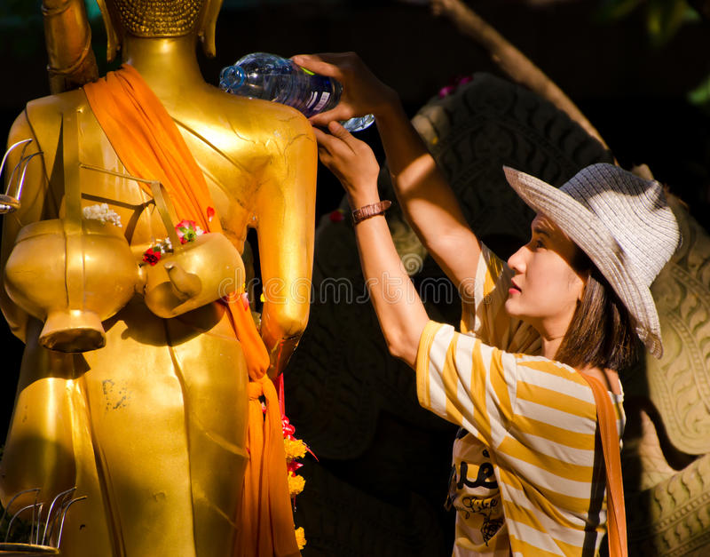 13 avril : femme versant la statue de Bouddha photo stock