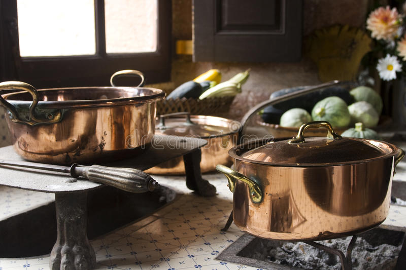 17th century cooking. Copper pans on 17th century coal stove in preserved kitchen in an old chateau in Burgundy, France. Still life with fruit and natural light stock images