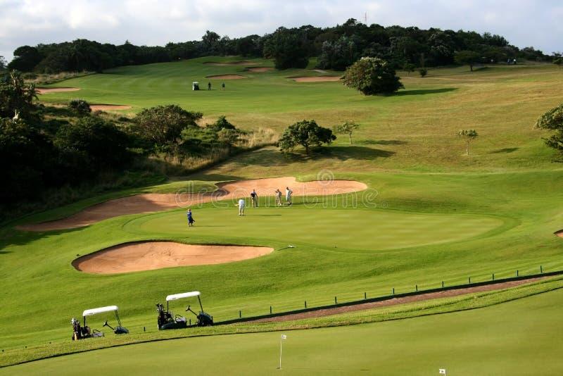 18o Verde de colocação do furo no campo de golfe com carros de golfe imagem de stock royalty free