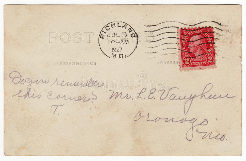 1920's Postcard Back with Red Stamp. Back of a 1927 souvenir postcard. Natural tone with cursive text. Red 2 cent stamp canceled with flag stamp. Addressed with royalty free stock photos