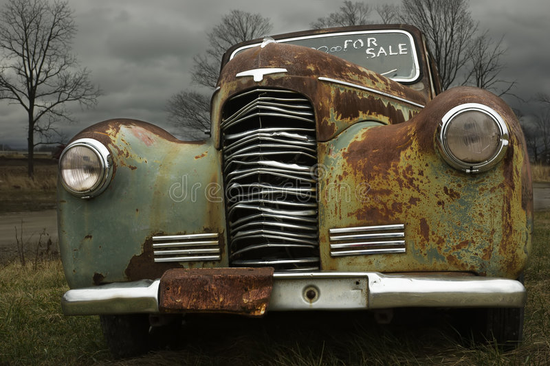 1930's Antique car. That's rusting in a field hoping to be sold stock image