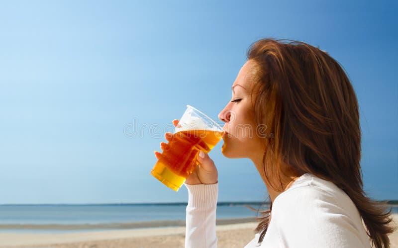 2个海滩饮用的女孩开会 免版税库存照片