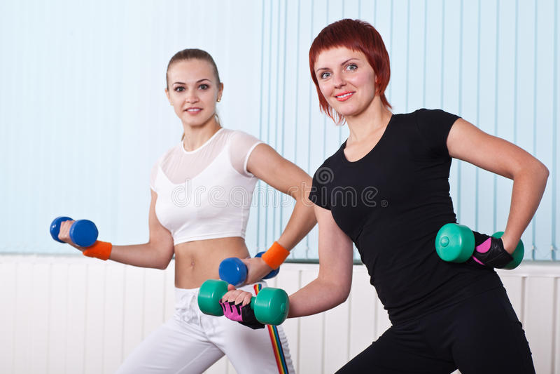 2 женщины пригодности поднимая гантели стоковое изображение