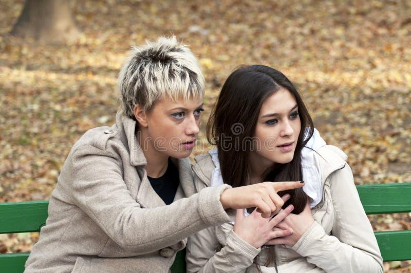 2 женщины шепча и ся стоковое фото