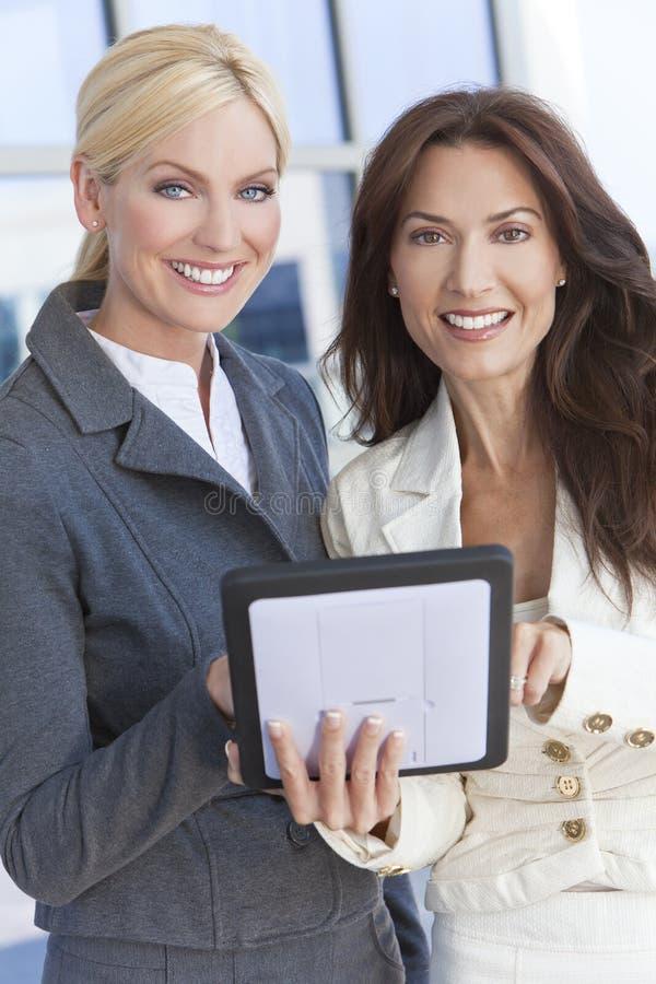 2 коммерсантки или женщины используя компьютер таблетки стоковые фотографии rf