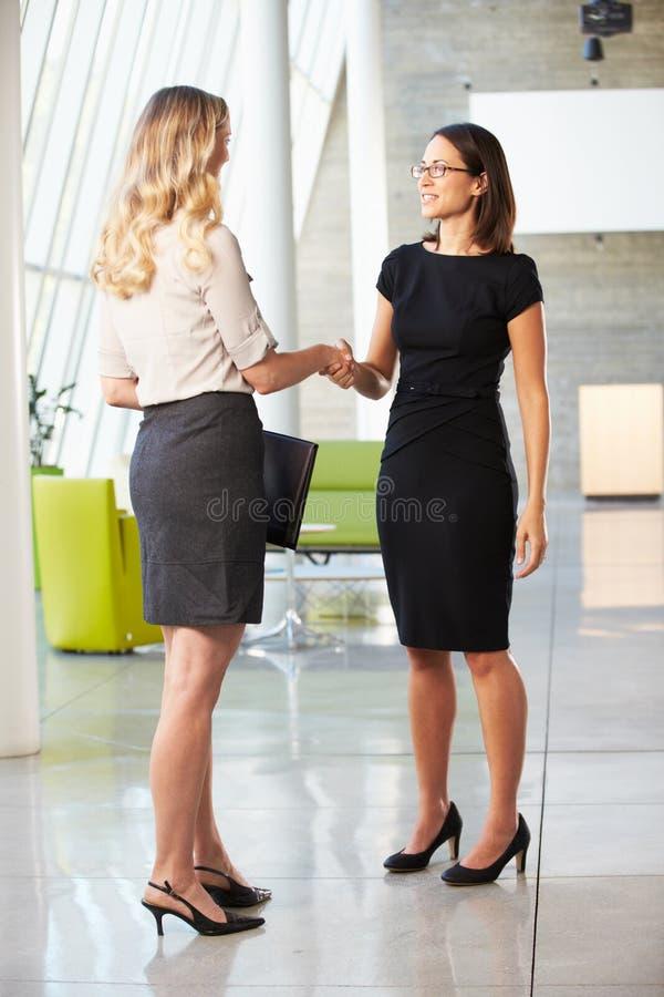 2 коммерсантки трястия руки в самомоднейшем офисе стоковые изображения rf