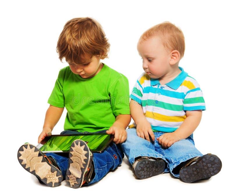 2 малыша играя таблетку стоковое изображение rf