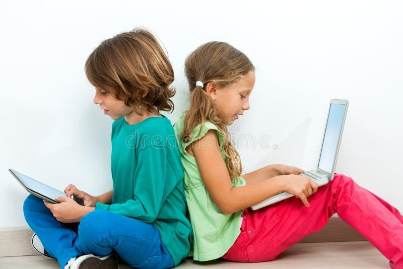2 малыша общаясь с компьтер-книжкой и таблеткой. стоковые фото