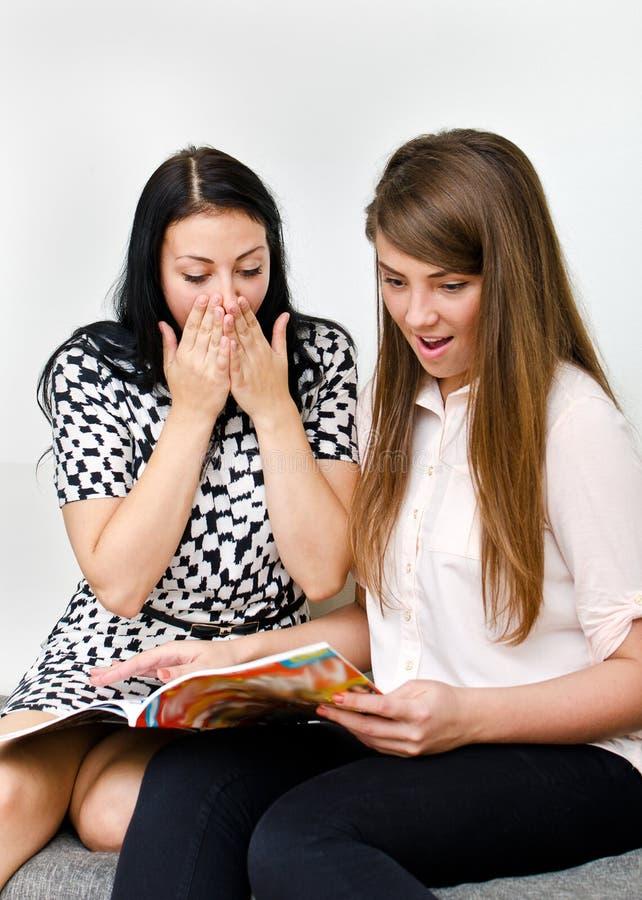 2 милых девушки читая кассету стоковое фото