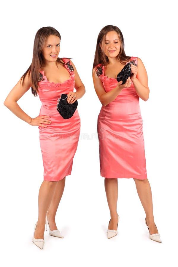 2 таких же женщины нося платье вечера в студии стоковая фотография