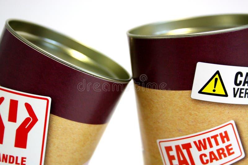 2 консервной банки с жирными предупреждающими стикерами
