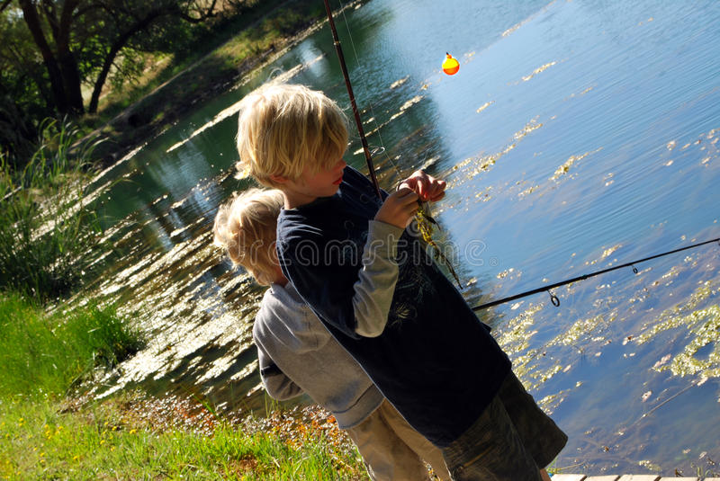 2 Boys Fishing. Two young boys fishing at a pond royalty free stock photos